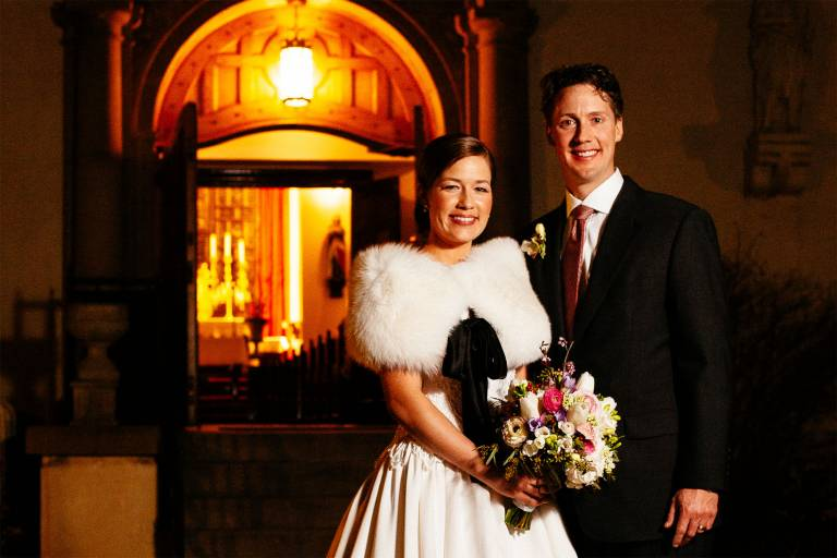 Bride and groom stand outside the Pauline Chapel at night.