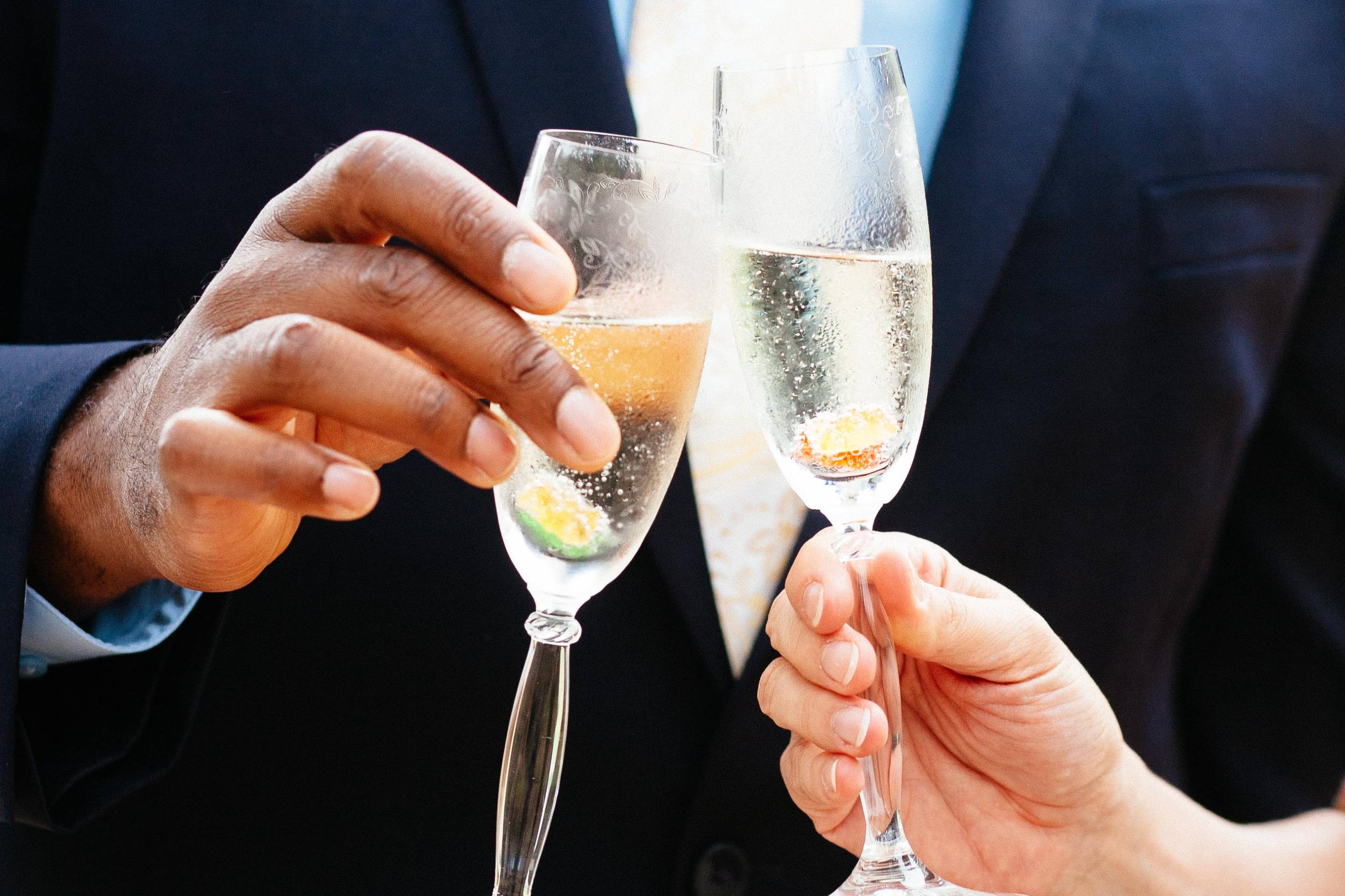 Couple holding champagne glasses and toasting.