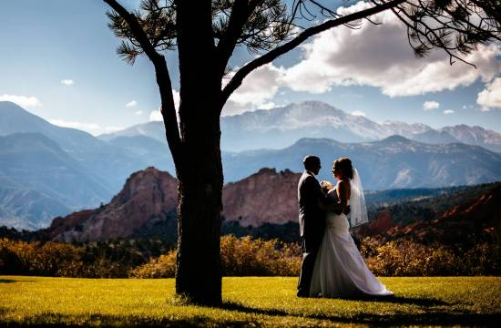 Wedding couple embraces in front of Pikes Peak.