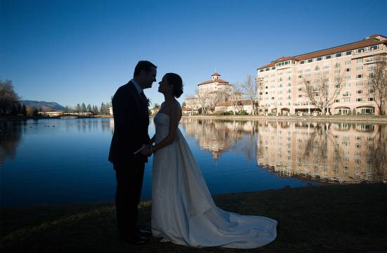 Bride and groom kiss beside the lake at The Broadmoor
