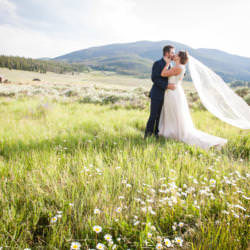 Bride and groom kiss in field of wildflowers at Keystone Ranch.