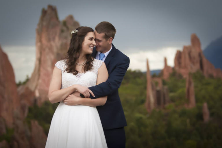 Bride and groom embracing in front of clouds and mountains at Garden of the Gods Park.