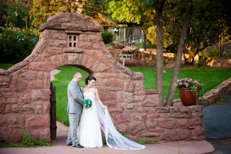 Bride and groom stand in front of stone doorway at the Craftwood Inn.