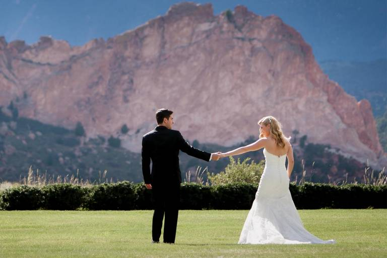 Wedding couple holds hands on the lawn at the Garden of the Gods Club.
