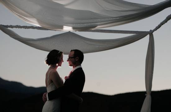 Wedding couple embraces underneath a chuppah.