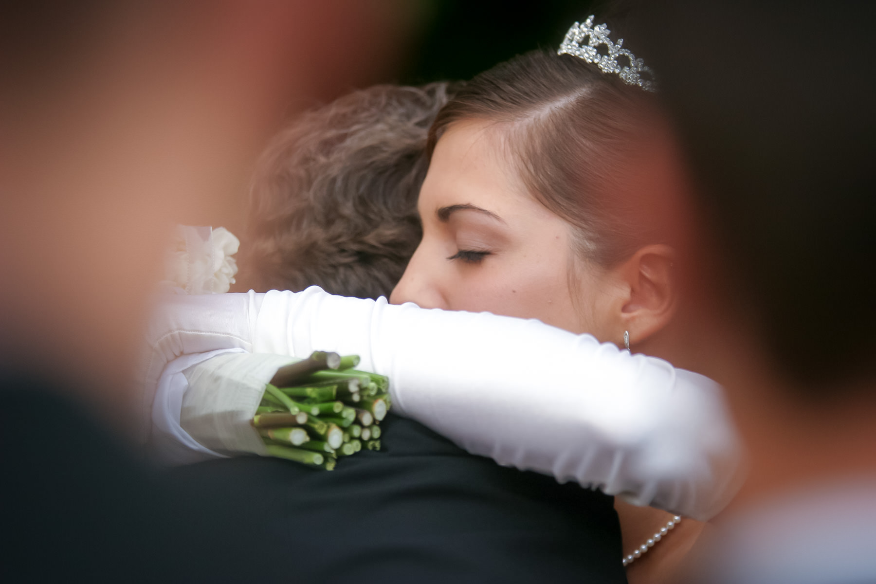 Bride hugs her father during wedding ceremony.