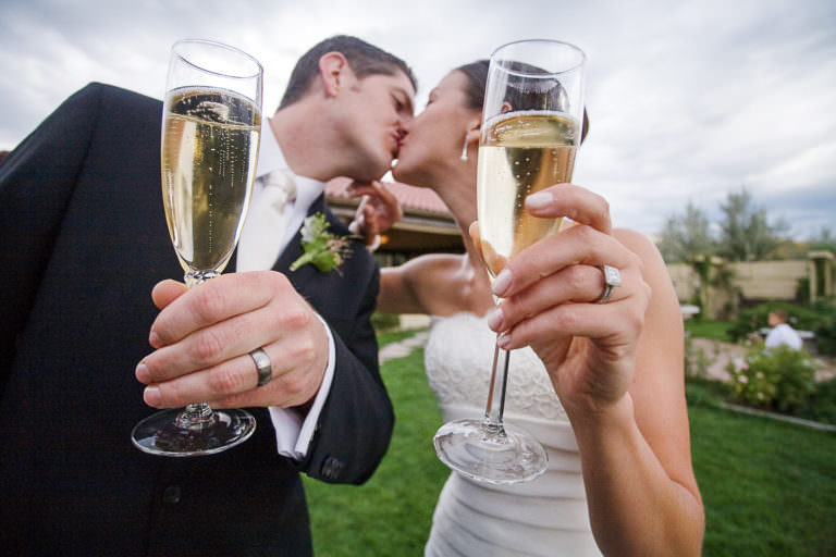 Bride and groom framed by champagne and wedding rings share a kiss at Hillside Gardens.