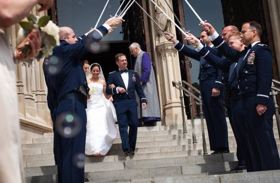 Wedding couple exits the National Cathedral underneath a saber arch.