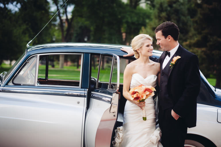 Bride and groom stand at the rear door of Rolls Royce