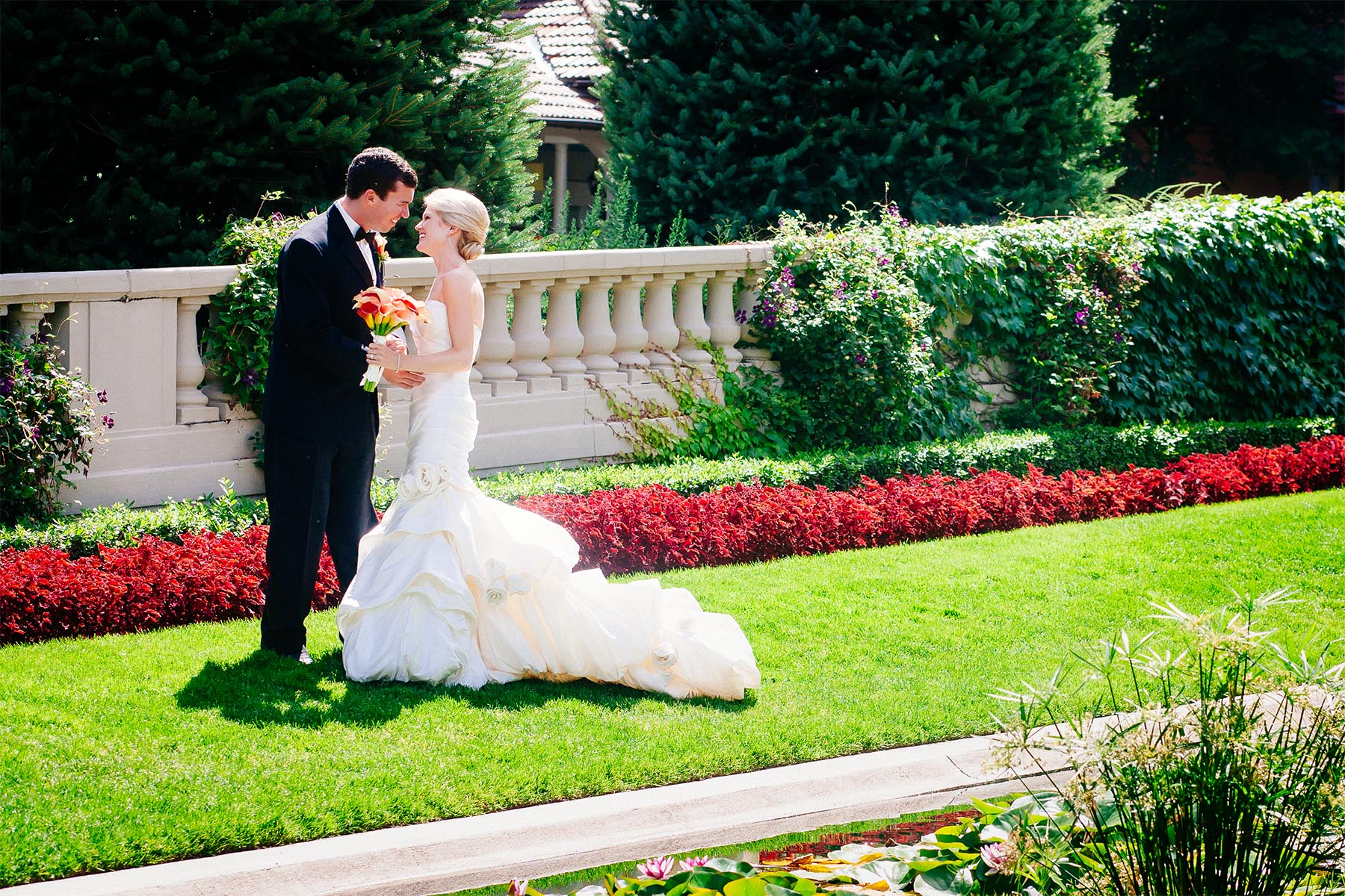 Wedding couple walks together in front of the koi pond at The Broadmoor.