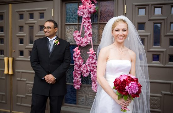 Bride and groom with monogrammed flowers at St. Paul Catholic Church