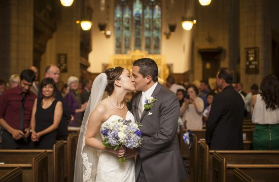 Bride and groom kiss as they exit ceremony at Grace Episcopal Church.