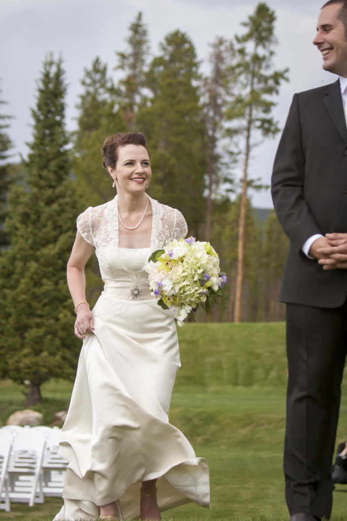 Bride walking to see groom before wedding ceremony at Keystone Ranch.