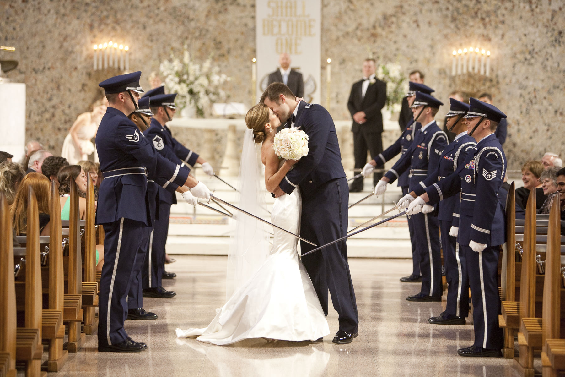 Bride and groom kiss at the saber arch during their wedding at the Air Force Academy Cadet Chapel.