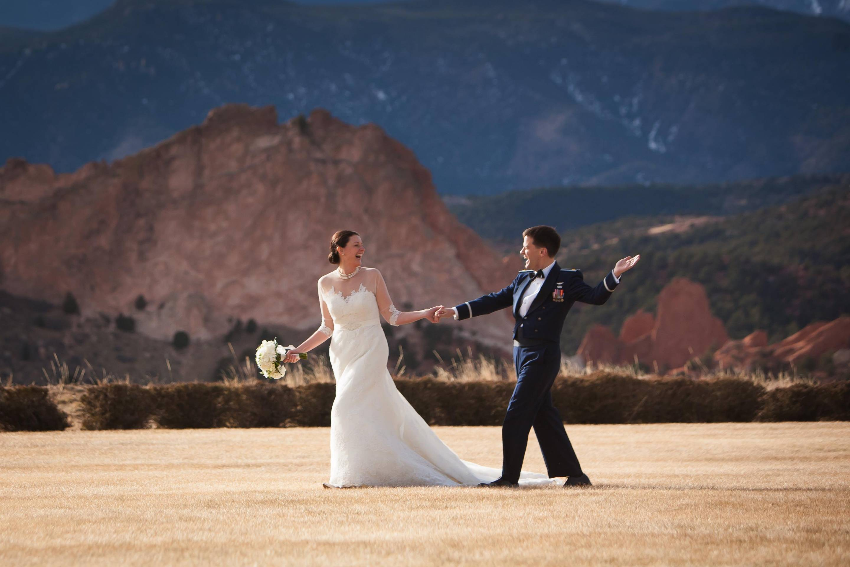 Wedding couple walk together and smile in front of the Garden of the Gods.