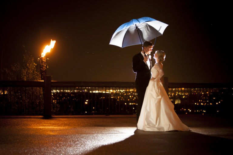 Night shot of bride and groom with umbrella, torch and city lights Cheyenne Lodge.
