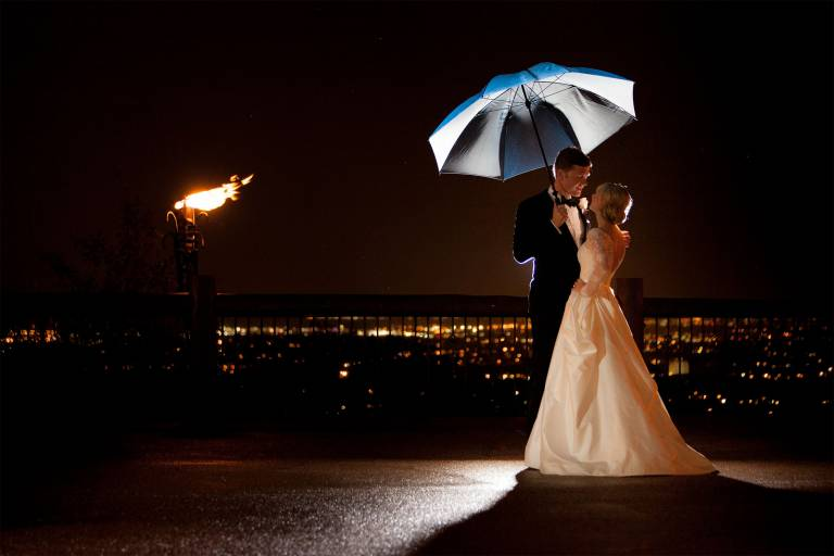 Couple at night embrace in the rain outside Cheyenne Lodge at The Broadmoor.