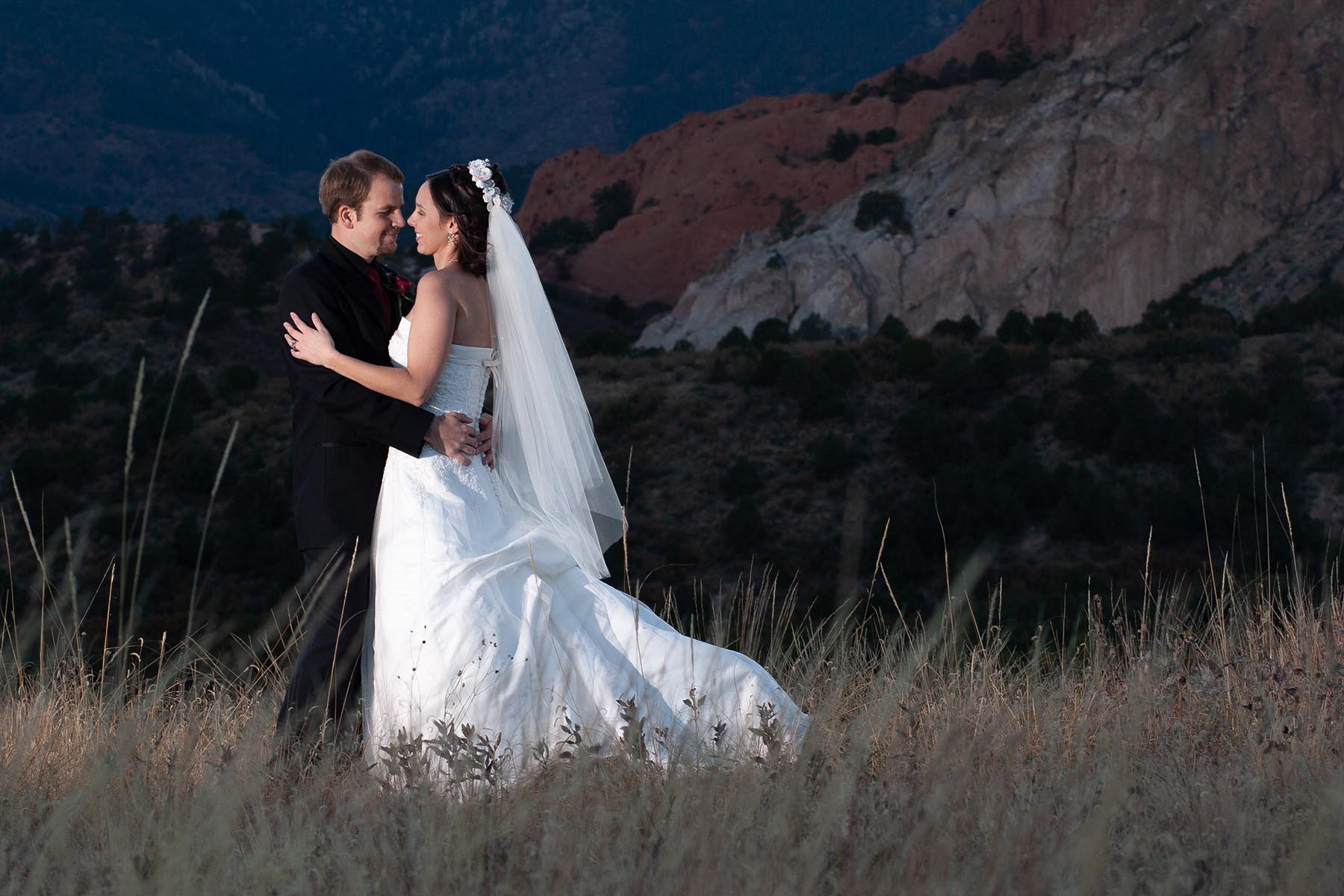 Wedding couple embraces in front of the Garden of the Gods.