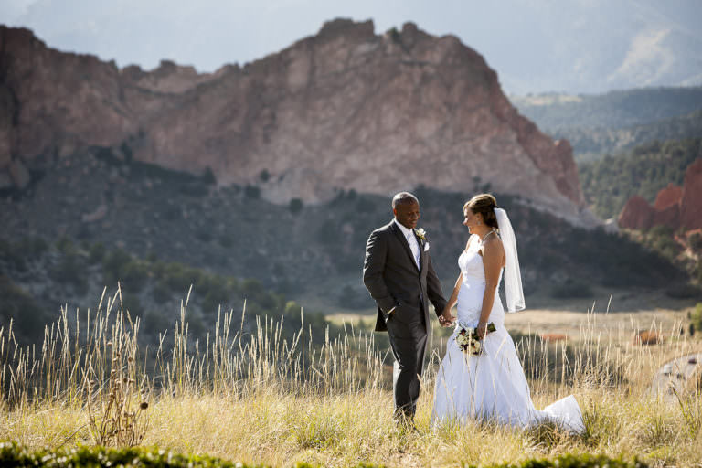 Bride and groom hold hands and stand in front of Garden of the Gods park and Pikes Peak.