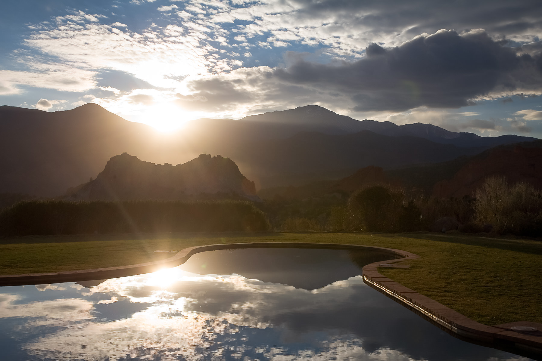 Sunset with blue sky and scattered clouds over the reflection pool at the Garden of the Gods Club and Resort with Garden of the Gods Park and Pikes Peak.