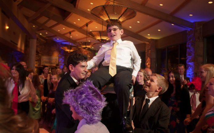 Boy lifted during horah at Bar Mitzvah reception at the Garden of the Gods Club.