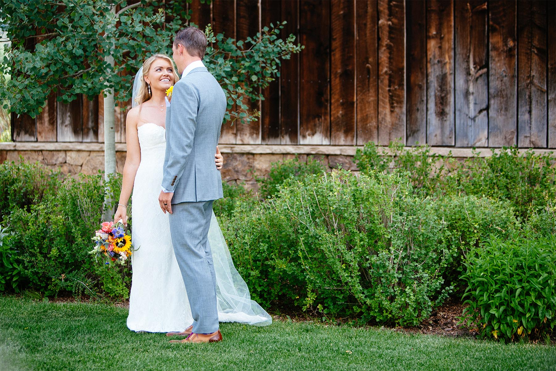 Wedding couple embraces in front of Old Thompson Barn.