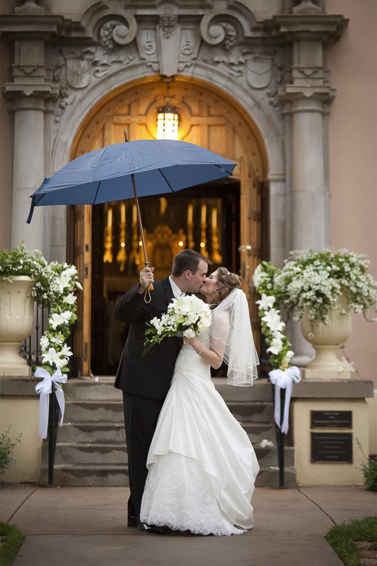 Bride and groom kiss underneath umbrella in front of Pauline Memorial Chapel.