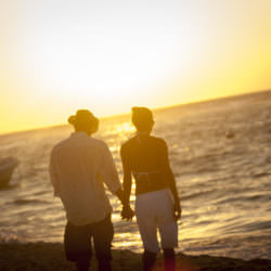 Couple walking together on the beach during a sun rise.