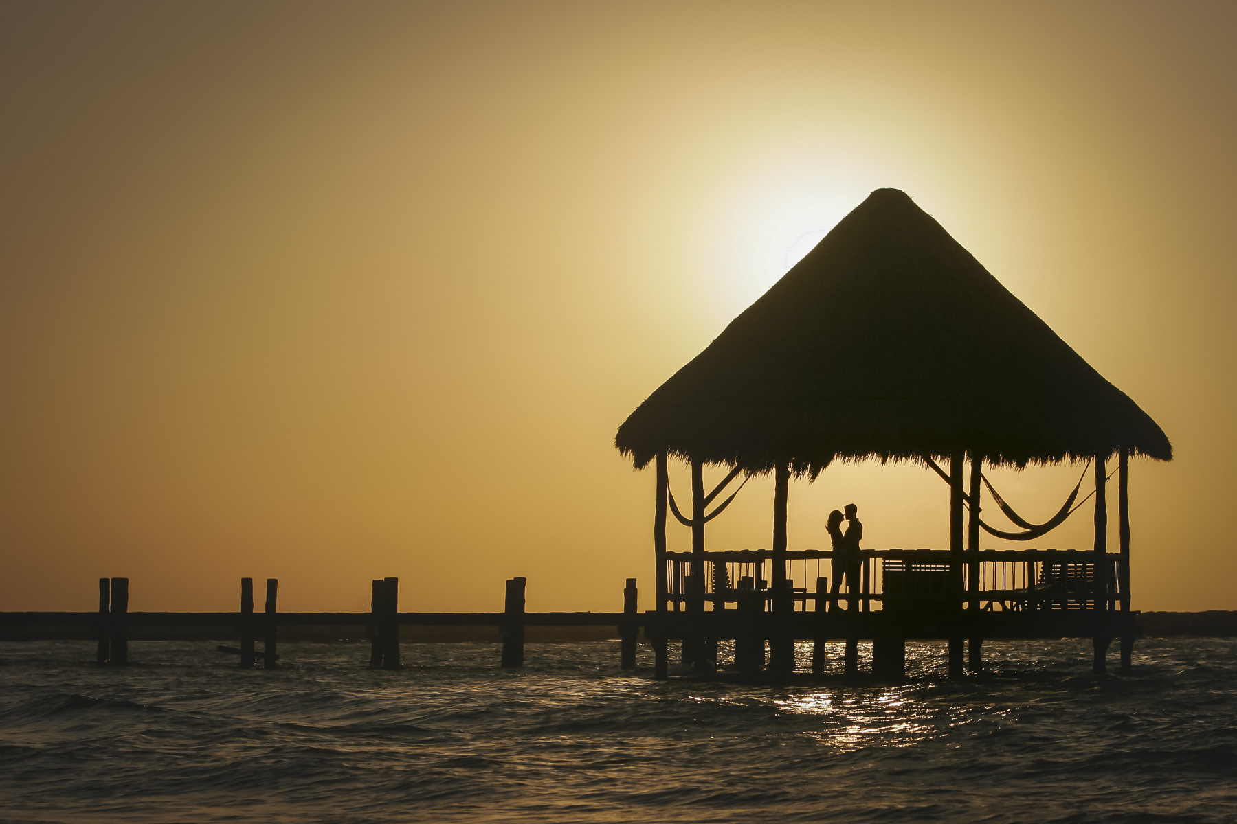 Man and woman on ocean pier embrace during sun rise.