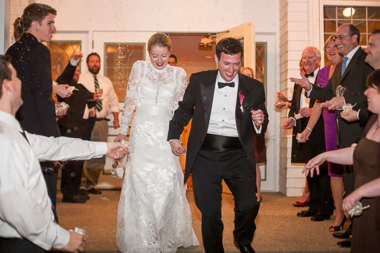 Bride and groom exit to tossed birdseed at the Cheyenne Mountain Country Club at the end of their wedding reception.