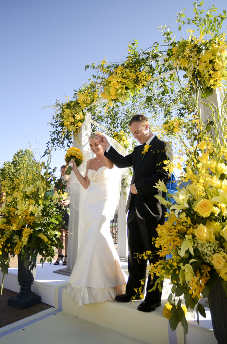 Bride and groom under yellow rose arch exit their ceremony on the Lakeside Terrace.
