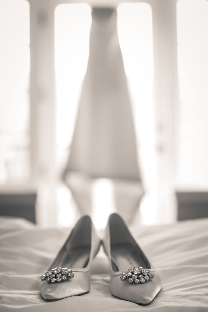Black and white of wedding shoes and wedding dress in bridal suite at The Broadmoor.