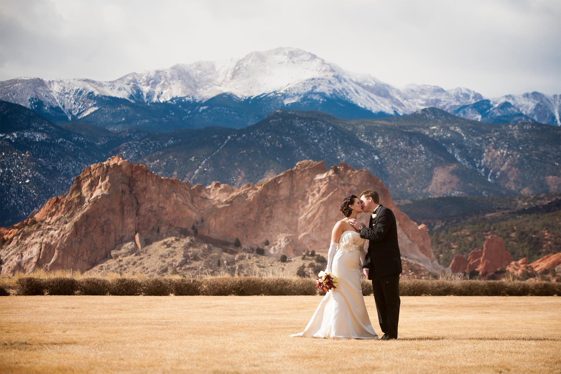 Wedding couple kisses in front of snow capped Pikes Peak.