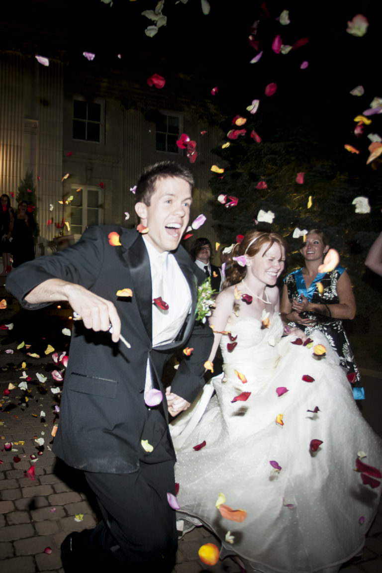 Bride and groom exiting their wedding reception with tossed rose petals.