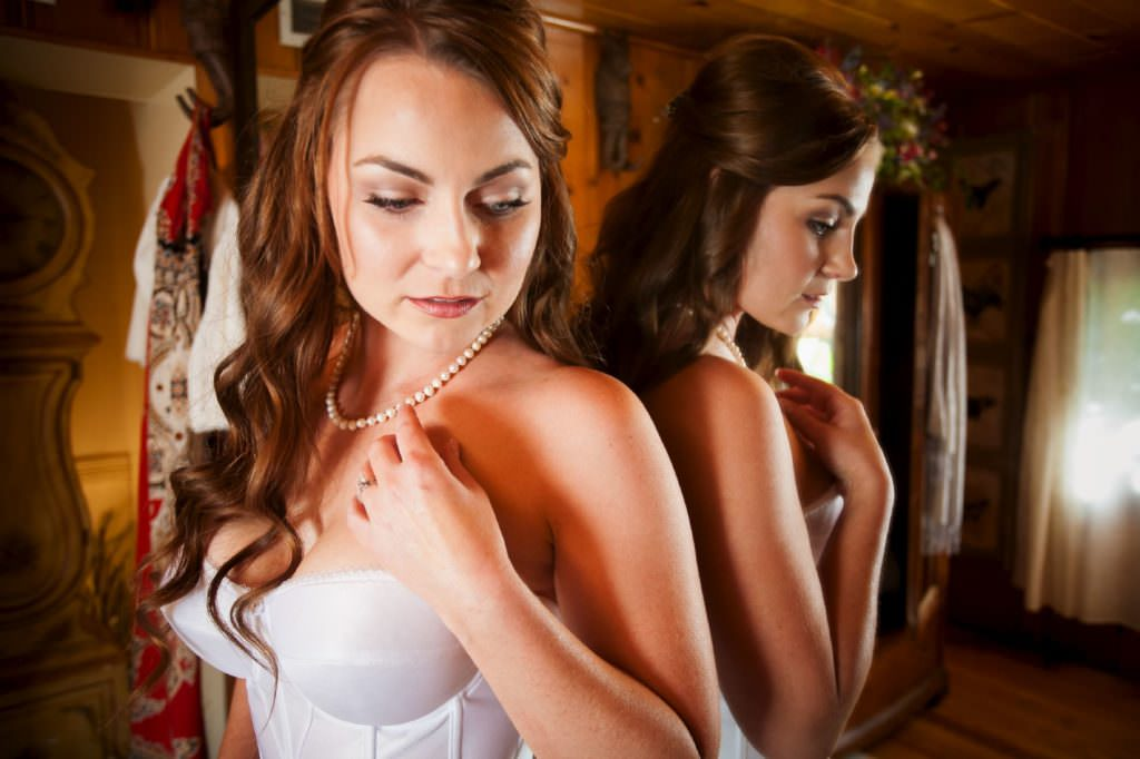 Bride wearing corset and pearl necklace inside Bride's Cottage at Craftwood Inn.
