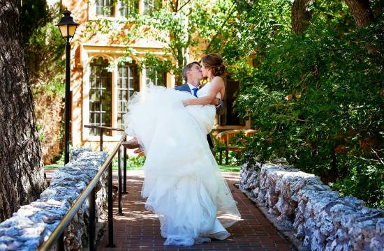Groom holds bride in the air and kisses her at the Glen Eyrie.