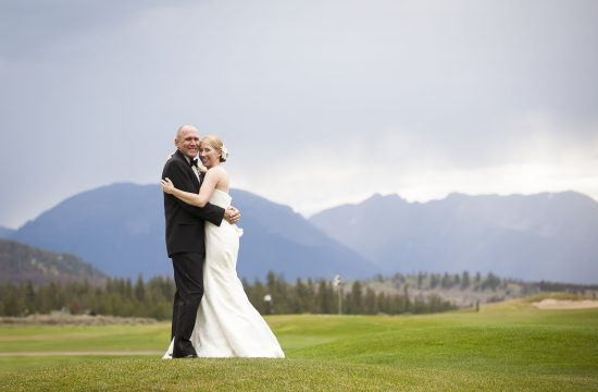 Bride and groom hold each other on the golf course at Keystone Ranch.