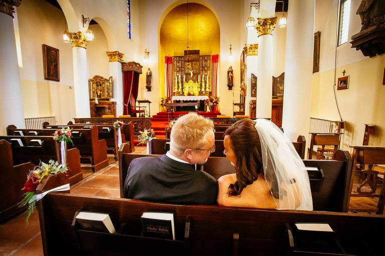 Bride and groom sit in pew at the Pauline Chapel on their wedding day.
