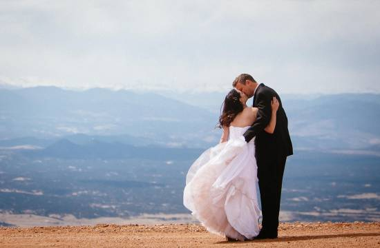Wedding couple kiss on top of Pikes Peak.