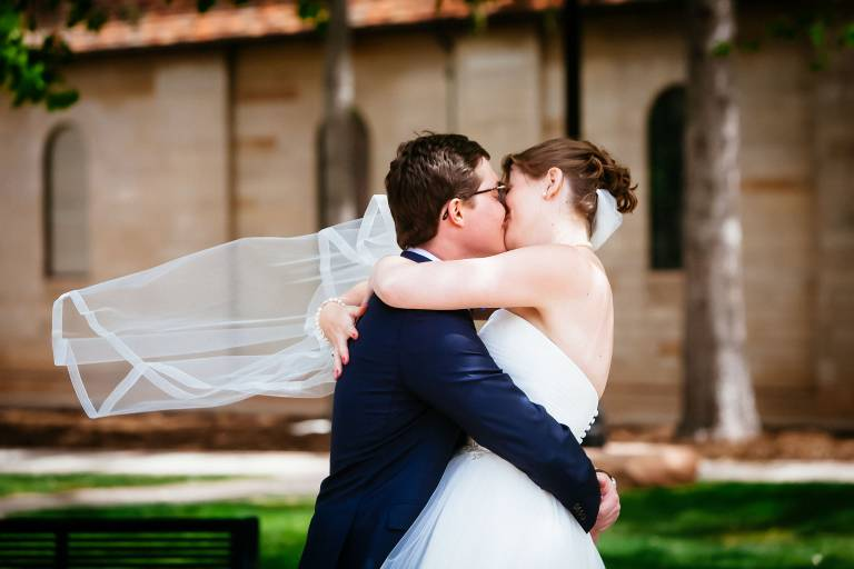 Couple embraces and kiss outside of Shove Chapel on their wedding day.