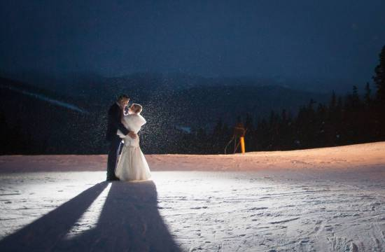 Wedding couple embrace in the snow at the top of Keystone Resort.