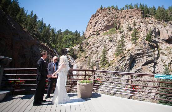 Couple holding hands during wedding ceremony at Seven Falls.