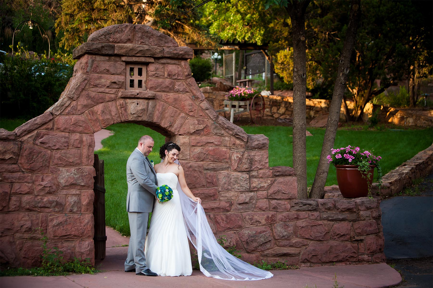 Wedding couple at the stone entrance to the Craftwood Inn.