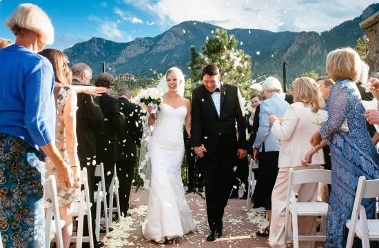 Wedding couple exits ceremony at Cheyenne Lodge as guests throw white rose petals.
