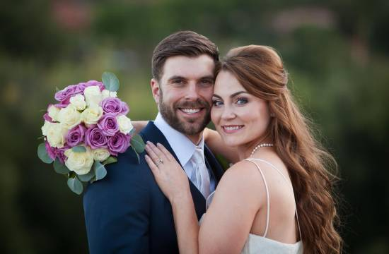 Portrait of wedding couple with purple and white bouquet.