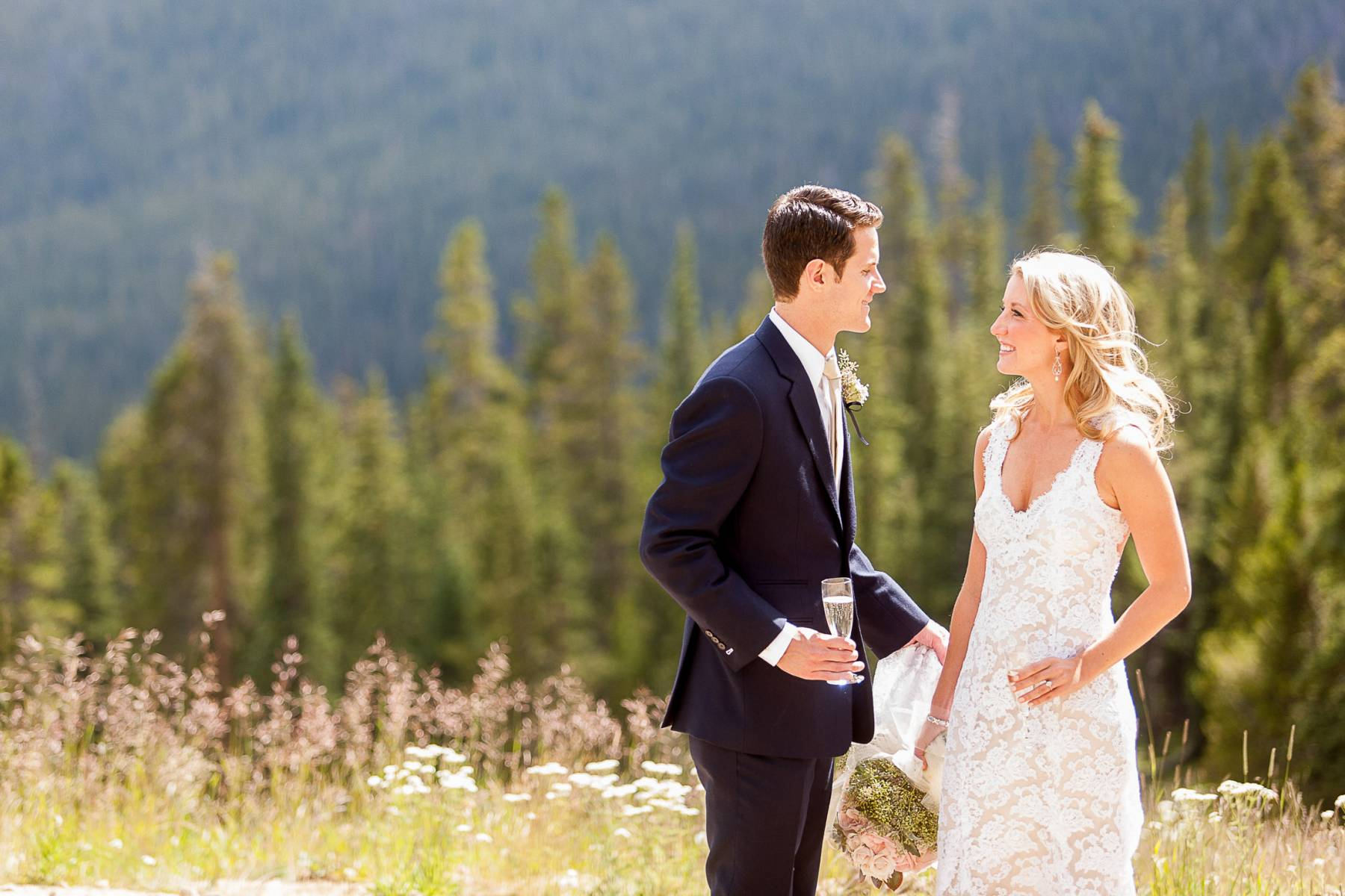 Wedding couple with Champagne on the hillside at Timber Ridge Lodge.