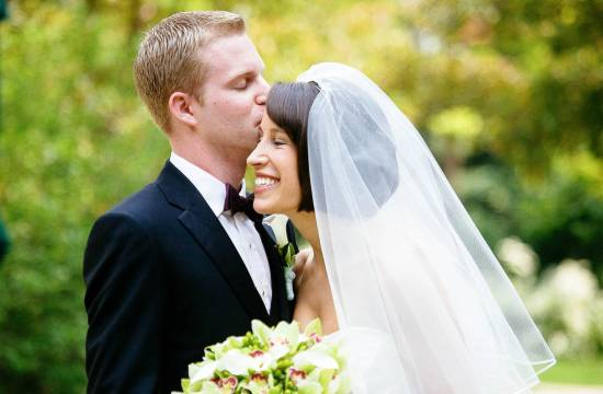 Groom kisses bride as she smiles and holds bouquet.