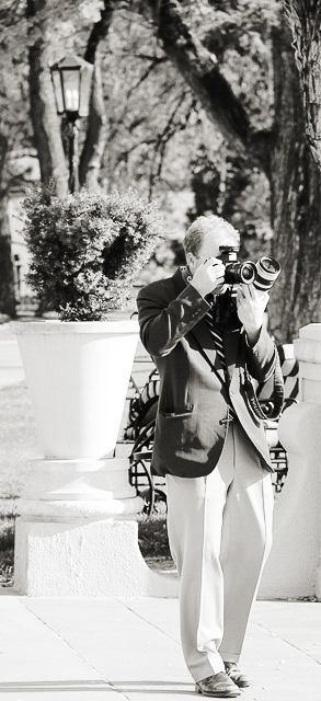 Man in suit and tie photographing a wedding