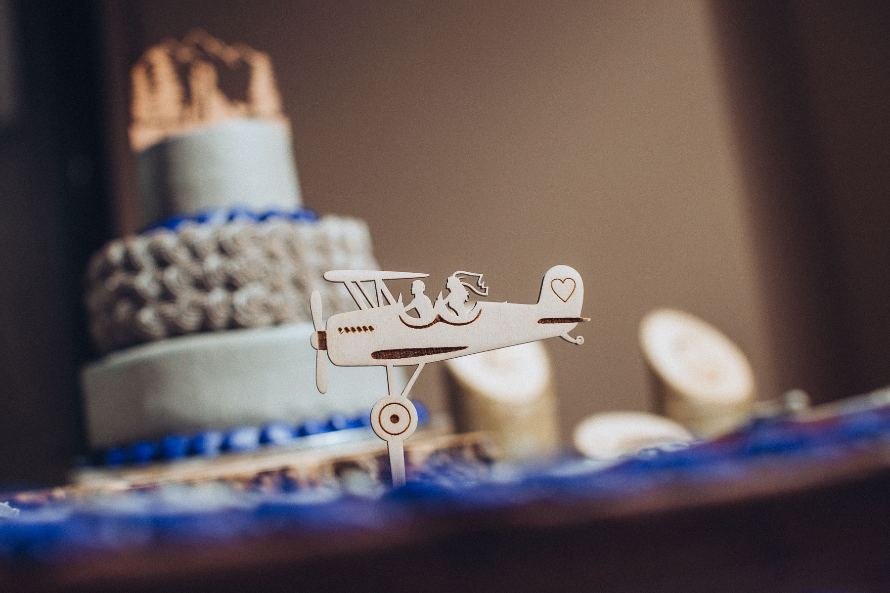 Wooden cake topper showing bride and groom riding in airplane.