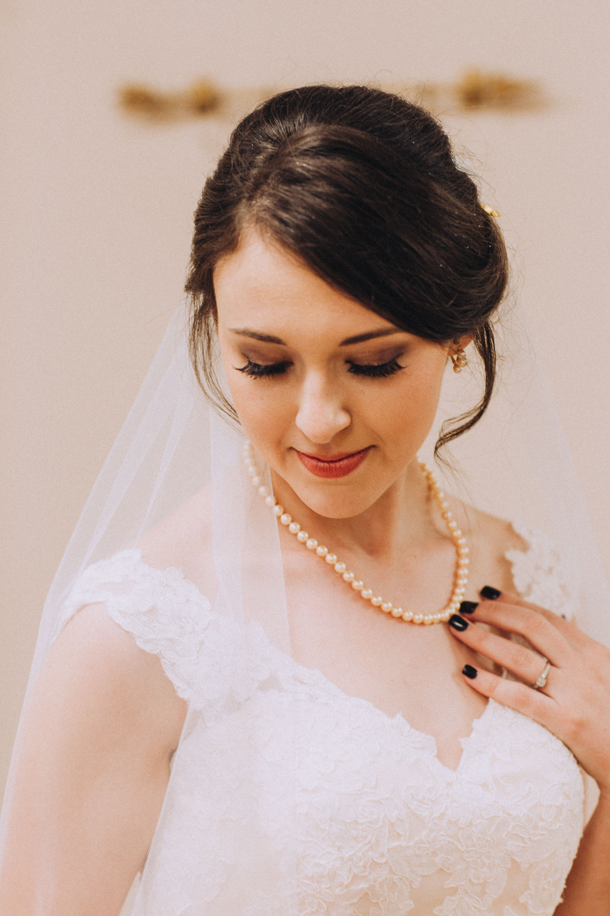 Portait of bride looking down and holding her pearl necklace.